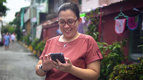 Woman holding and using a smartphone